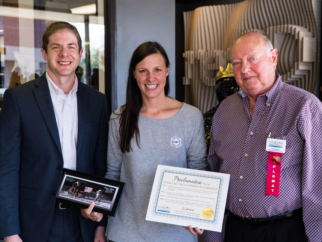 A smiling woman stands between two men. She is holding a plaque and a certificate.