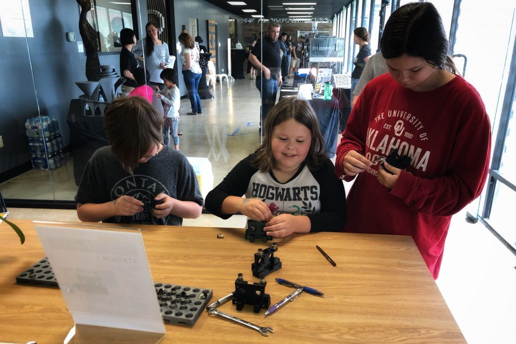 Three kids sit at a table with tools and build part of a 3D printer. A crowd of people is in the background.