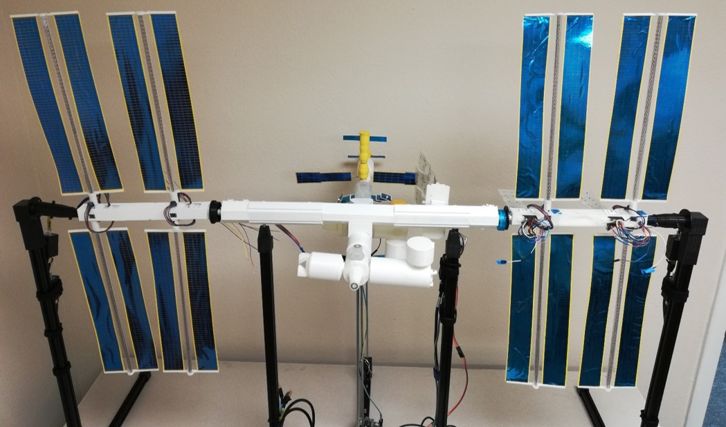 ISS Mimic, a 100th scale model of ISS, sits on a table. You can see 3d printed tubes, wires connecting to motors and large, foil covered solar arrays.