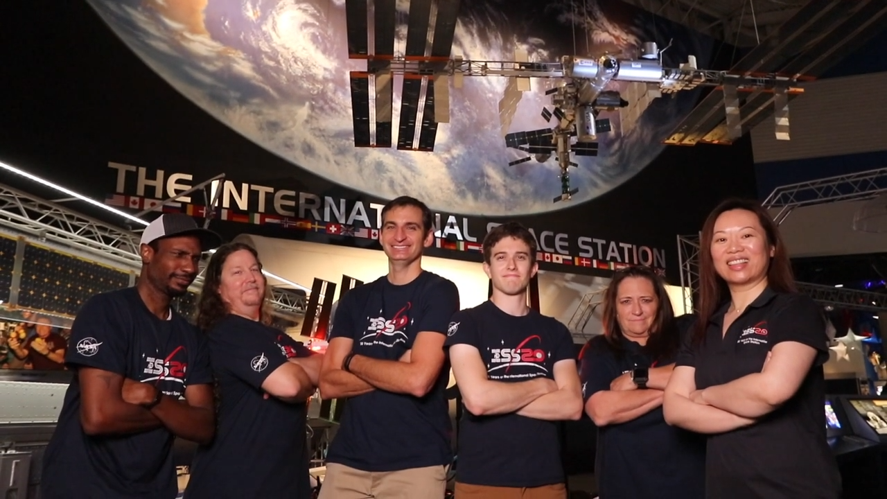 "Six people, four men and two women stand in front of a display of the earth with the ISS floating above their heads. All of them are wearing tshirts that read ""ISS20"""