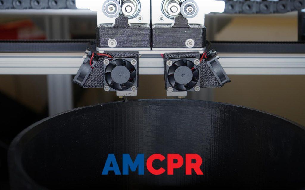 A gigabot 3d printer, printing a black 8 inch coupling.